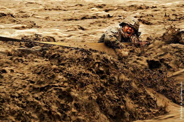 U.S. Army Staff Sgt. Patrick Reynolds, Security Forces squad leader attached to Provincial Reconstruction Team Zabul, fights racing water while holding onto a tow strap attached to an Afghan National Army vehicle stuck in the Lurah River in Afghanistan's Shinkai District