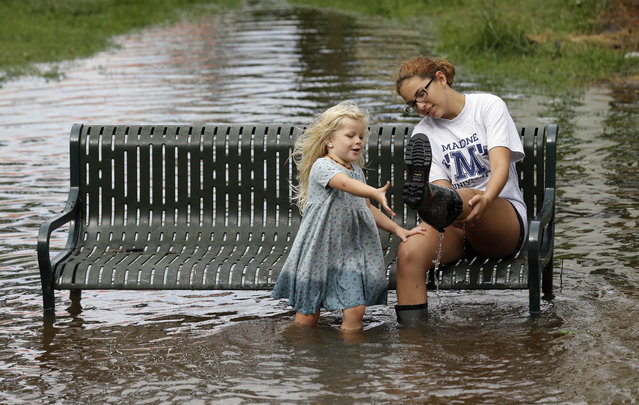 Katie Bender gets some assistance from Johanna Bender, left, as they dump water from a boot while sitting on a flooded street after Hurricane Arthur passed through in Manteo, N.C., Friday, July 4, 2014. Arthur began moving offshore and away from North Carolina's Outer Banks early Friday after hitting the state's barrier islands overnight, creating a Fourth of July holiday that saw flooding and tens of thousands of power outages. (Photo by Gerry Broome/AP Photo)