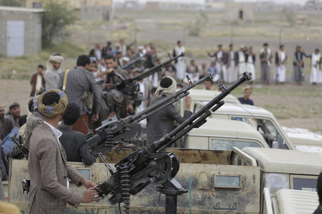 In this August 1, 2019, file photo, Houthi rebel fighters ride on trucks mounted with weapons, during a gathering aimed at mobilizing more fighters for the Houthi movement, in Sanaa, Yemen. Airstrikes by the Saudi-led coalition fighting Yemen's rebels Houthi  hit a detention center in southwestern province of Dhamar, officials and the rebels' health ministry said Sunday. (Photo by Hani Mohammed/AP Photo/File)