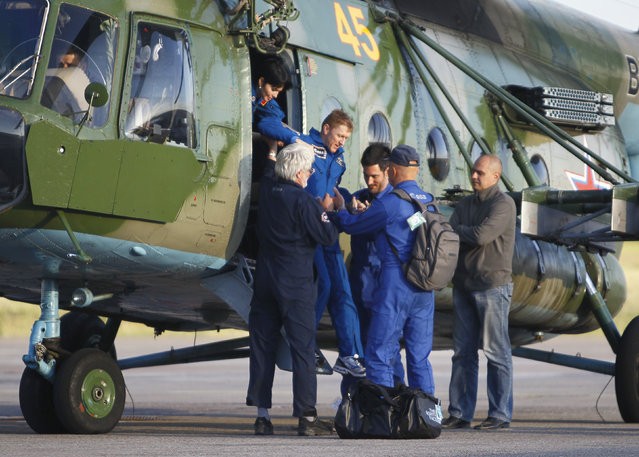 International Space Station crew member, Britain's Tim Peake, is assisted by ground personnel as he walks out of a helicopter upon his arrival at the airport of Karaganda, Kazakhstan, Saturday, June 18, 2016. (Photo by Shamil Zhumatov/Pool Photo via AP Photo)