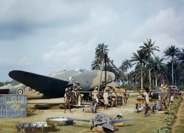 Local workers helping RAF fitters change the engine of a Lockheed Hudson at Yundum in the Gambia, April 1943. (Photo by Ted Dearberg/IWM/PA Wire)