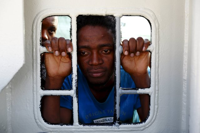 Migrants look out of a window on the Medecins Sans Frontiere (MSF) rescue ship Bourbon Argos as it arrives in Trapani, on the island of Sicily, Italy, August 9, 2015. Some 241 mostly West African migrants on the ship arrived on the Italian island of Sicily on Sunday morning, according to MSF. (Photo by Darrin Zammit Lupi/Reuters)