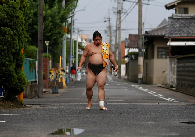 """Sumo wrestler Kainishiki returns to training at Ganjoji Yakushido temple in Nagoya, Japan on July 18, 2017. Full assimilation into Japanese culture means that foreign wrestlers face no ill-will. """"We wear our topknots, kimonos and sandals, and live by Japanese rules, and the rules of sumo"""", said Tomozuna Oyakata. """"It's only by chance that we were born a different nationality"""". (Photo by Issei Kato/Reuters)"""