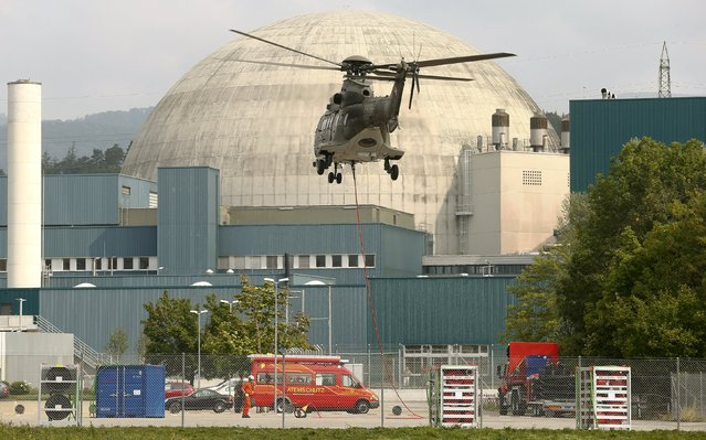 A Swiss air force helicopter flies, during an exercise, in front of the reactor building of the Swiss nuclear power plant Goesgen near the town of Daeniken west of Zurich August 11, 2015. (Photo by Arnd Wiegmann/Reuters)