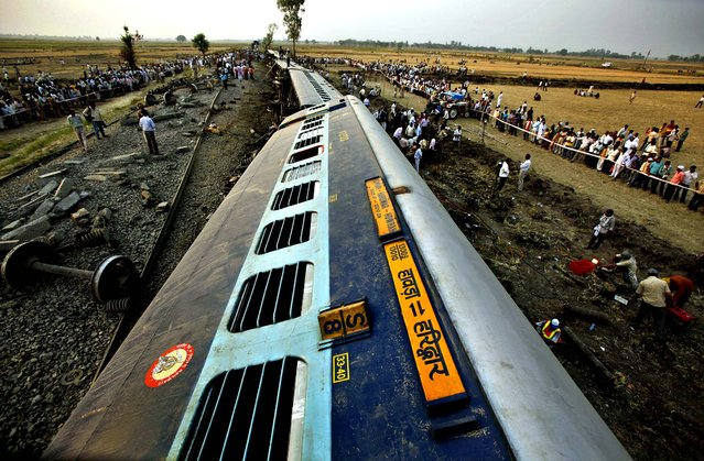 Officials and locals gather around the fallen compartments of Doon Express, a passenger train which derailed in Jaunpur, India on May 31, 2012