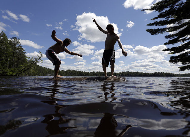 Ben Boschetto of Wayland, Mass., left, and Wes Bell of Fort Ann, N.Y., try to force each other into the water while log birling on Lower St. Regis Lake at the Adirondack Woodsmen's School at Paul Smith's College on Thursday, July 10, 2014, in Paul Smiths, N.Y. (Photo by Mike Groll/AP Photo)