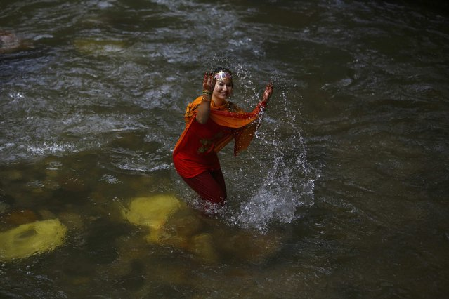 "A Hindu devotee plays with water during the ""Bol Bom"" (Say Shiva) pilgrimage in Kathmandu July 21, 2014. The faithful, chanting the name of Lord Shiva, run about 15 km (9 miles) barefooted toward Pashupatinath temple seeking good health, wealth and happiness. (Photo by Navesh Chitrakar/Reuters)"