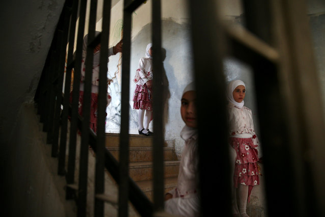 Girls wait on a staircase during a celebration marking the end of the school year in the town of Douma, eastern Ghouta in Damascus, Syria May 21, 2016. (Photo by Bassam Khabieh/Reuters)