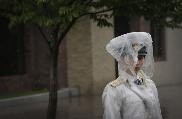 A traffic controller stands in her rain gear Friday, July 25, 2014 in Pyongyang, North Korea. A typhoon was approaching North Korea on Friday as the country began its rainy season. (Photo by Wong Maye-E/AP Photo)