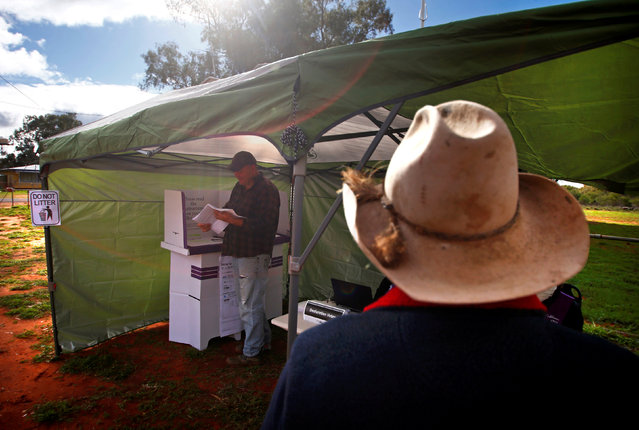 Farmer Darrell Peirpoint watches as a local resident votes in the remote voting station in the western New South Wales outback town of Enngonia, Australia, June 22, 2016. (Photo by David Gray/Reuters)