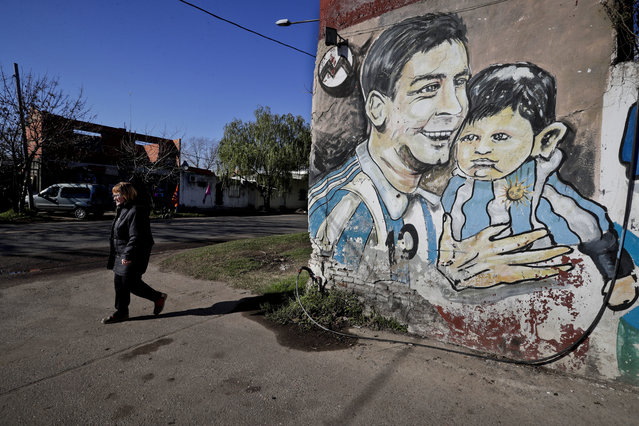 A woman walks by graffiti of Lionel Messi painted near the house where the soccer star grew up in Rosario, Argentina, Friday, June 30, 2017. Some 260 guests, including teammates and former teammates of the Barcelona star, are expected to attend the highly anticipated wedding between Messi and Antonella Roccuzzo later Friday. (Photo by Victor R. Caivano/AP Photo)