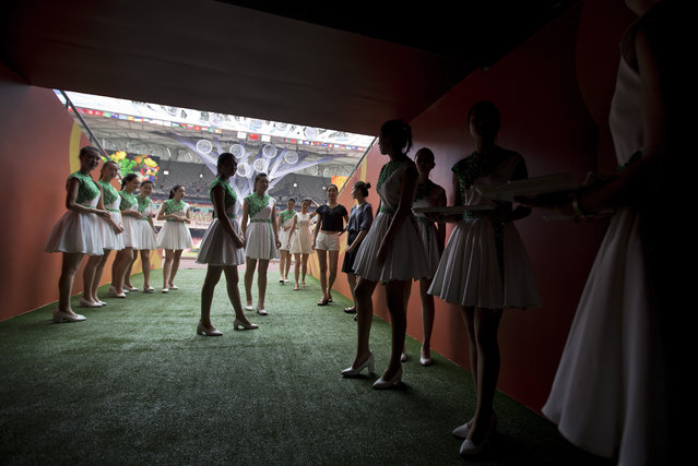 Attendants prepare to walk into the iconic Bird's Nest National Stadium during a rehearsal of medal presentation ceremonies for the upcoming 15th IAAF Athletics World Championships in Beijing Tuesday, Aug. 18, 2015. The sport event will be held in Beijing from August 22 to 30. (Photo by Andy Wong/AP Photo)