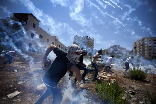 Palestinians run for cover during clashes with Israeli soldiers following a protest against the war in the Gaza Strip, outside Ofer, an Israeli military prison near the West Bank city of Ramallah, on August 1, 2014. (Photo by Majdi Mohammed/Associated Press)