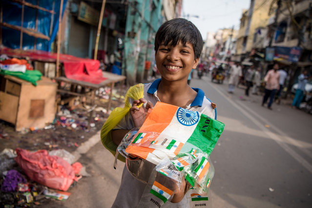 A boy smiles while posing for a photo with Indian flags in his hands on India's 71st independence day on August 15, 2017 in Delhi, India. India celebrated its 71st Independence Day today. Indian national flag or its colors are printed on various objects that people display on the occasion. (Photo by Shams Qari/Barcroft Images)