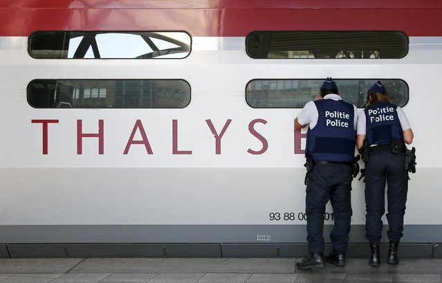 Belgian police officers inspect a Thalys high-speed train at Brussels Midi/Zuid rail station, August 22, 2015. A machine gun-toting attacker wounded three people on a high-speed train in France on Friday before being overpowered by passengers who included an American soldier. (Photo by Francois Lenoir/Reuters)
