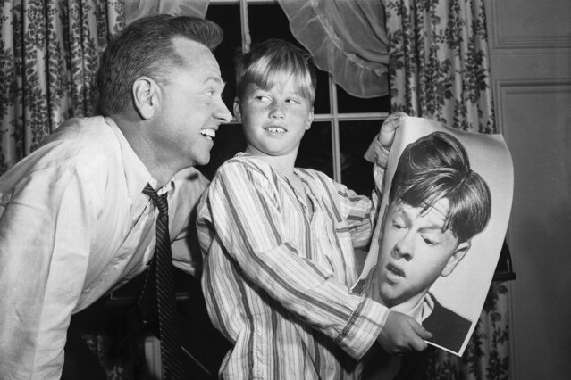 "Actor Mickey Rooney and his son, Teddy, are looking at an old photo of Mickey, taken when he starred in the Andy Hardy series, 1958. Mickey and Teddy are shown on the set of ""Andy Hardy Comes Home"", a sequel of Andy Hardy and Mickey plays the father in the movie. (Photo by Bettmann Archive)"