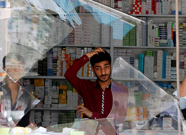 An Afghan shopkeeper reacts behind the broken windows of his shop near the site of a suicide bomb attack in Kabul, Afghanistan on August 29, 2017. (Photo by Omar Sobhani/Reuters)