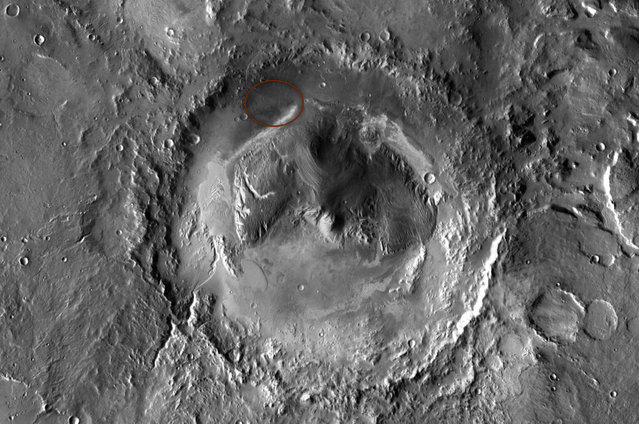 NASA has selected Gale crater as the landing site for the Mars Science Laboratory mission. The mission's rover will be placed on the ground in a northern portion of the crater in August 2012. This view of Gale is a mosaic of observations made in the visible-light portion of the spectrum by the Thermal Emission Imaging System camera on NASA's Mars Odyssey orbiter. Gale crater is 96 miles (154 kilometers) in diameter and holds a layered mountain rising about 3 miles (5 kilometers) above the crater floor. The ellipse superimposed on this image indicates the intended landing area, 12.4 miles (20 kilometers) by 15.5 miles (25 kilometers). The portion of the crater within the landing area has an alluvial fan likely formed by water-carried sediments. The lower layers of the nearby mountain – within driving distance for Curiosity – contain minerals indicating a wet history. (Photo by NASA/JPL-Caltech/ASU)