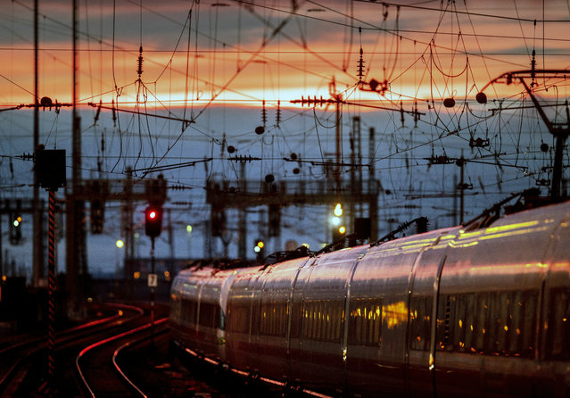 A train leaves the main train station after the sun set in Frankfurt, Germany, Friday, January 17, 2020. (Photo by Michael Probst/AP Photo)