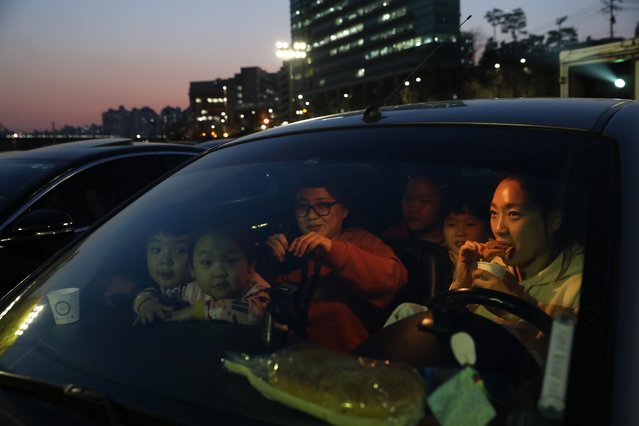 A family prepares to watch a movie from their car at a drive-in theater as South Koreans take measures to protect themselves against the spread of coronavirus (COVID-19) on March 23, 2020 in the Seongdong district of Seoul, South Korea. South Korea has called for expanded public participation in social distancing for the next two weeks, as the country witnesses a wave of community spread and imported infections leading to a resurgence in new cases of COVID-19. According to the Korea Center for Disease Control and Prevention on Monday, 64 new cases were reported. The total number of infections in the nation tallies at 8,961. (Photo by Chung Sung-Jun/Getty Images)