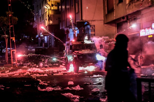 Millitants lobb fireworks towards an armoured police vehicle during clashes with Turkish police, on August 27, 2015 in the Gazi district in Istanbul. Five people, including two children and a soldier, were killed in clashes between Kurdish militants and security forces in Turkey's restive Kurdish-majority southeast on August 27, local officials and the army said. (Photo by Ozan Kose/AFP Photo)