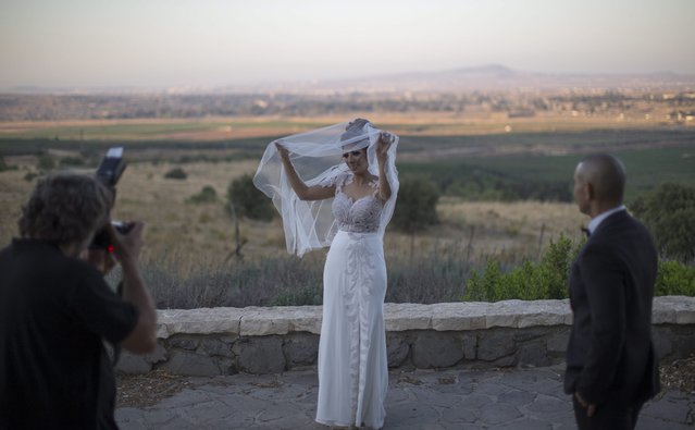 A newly marred couple during a photo session with the Syrian city of Quneitrain the (background, on the Israeli Syrian border in the center of the Golan Heights, 17 July 2016. An Israeli army spokesman announced that late afternoon an unmanned drone entered Israeli territory from Syria at the center of the Golan Heights. Israeli Air Force tried to intercept the drone with two Patriot missiles and one air-to-air missile, without hitting the target. (Photo by Atef Safadi/EPA)