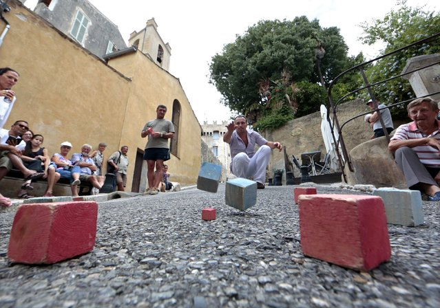 A competitor strikes a boule as he attends the square boules world championship in Cagnes, August 16, 2014. 330 competitors of different countries compete in this unique two days championship. (Photo by Eric Gaillard/Reuters)