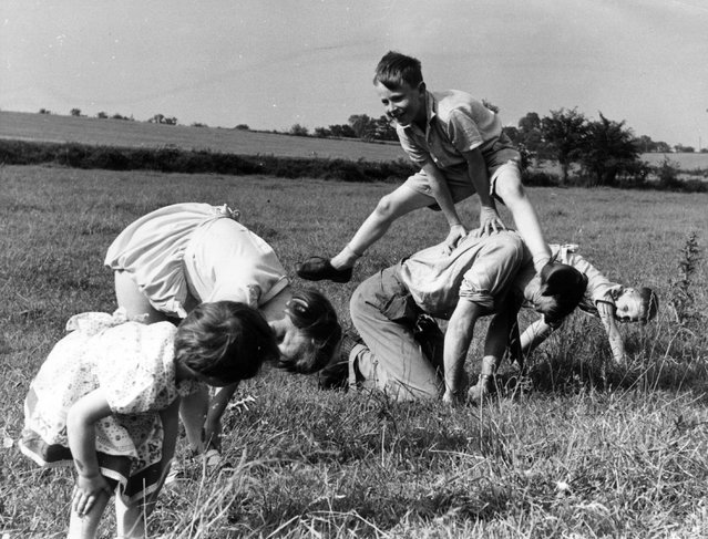A game of leap-frog in a field, May 1955. (Photo by Charles Hewitt)