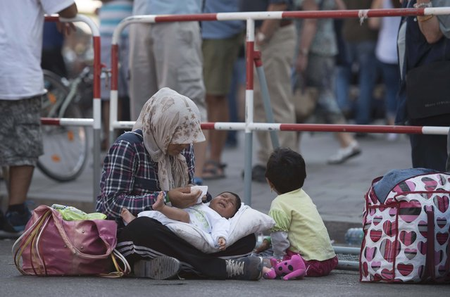 A migrant sits with her children outside the main railway station in Munich, Germany, September 1, 2015. (Photo by Lukas Barth/Reuters)
