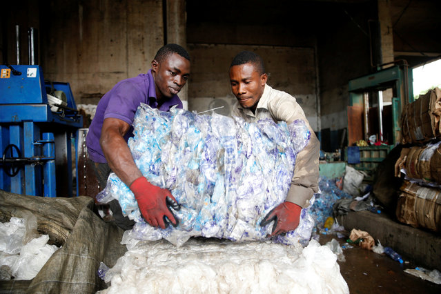 Men lift compressed waste from a machine at the Wecycler waste recycling centre in Ebutte Metta district in Lagos, Nigeria July 28, 2016. (Photo by Akintunde Akinleye/Reuters)