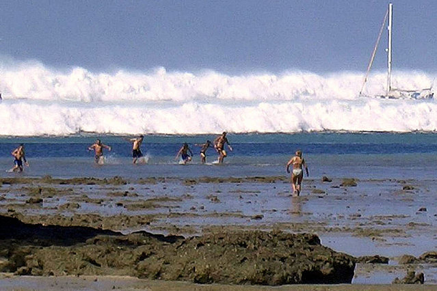 Krabi Province, Southern Thailand, December 26, 2004. Tourists caught by the first of six waves rolling towards Hat Rai Lay Beach, when the tsunami struck after the submarine earthquake registering 9.2 on the Richter Scale. (Photo by AFP Photo/Stringer)