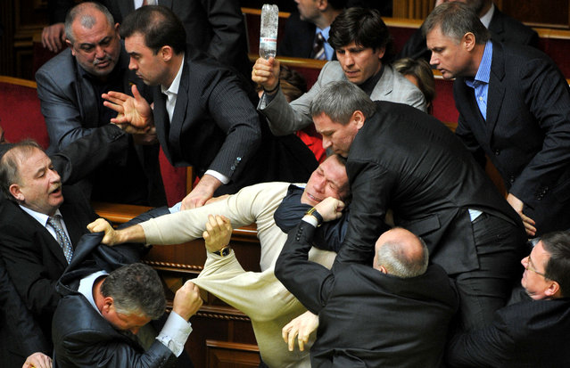 Deputies of Ukraine's parliament fight during a parliament sitting in Kiev on April 27,  2010. Fighting broke out and smoke bombs and eggs were thrown Tuesday as Ukraine's parliament erupted into chaos as it ratified a bitterly controversial deal with Russia extending the lease of a key naval base. The deal signed last week by Russian President Dmitry Medvedev and his Ukrainian counterpart Viktor Yanukovych had been slammed by the pro-Western Ukrainian opposition as a historic surrender of sovereignty. (Photo by Sergei Supinsky/AFP Photo)