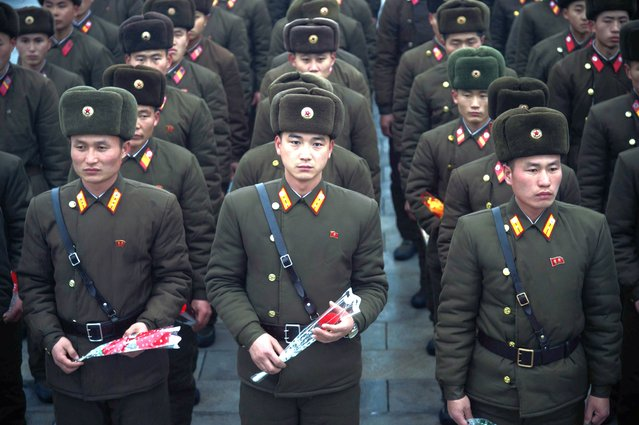 In a photo taken on December 17, 2019 Korean People's Army (KPA) soldiers hold flowers as they pay their respects before a statue of late North Korean leader Kim Jong Il, on the anniversary of his death, at Mansu Hill in Pyongyang. (Photo by Kim Won Jin/AFP Photo)