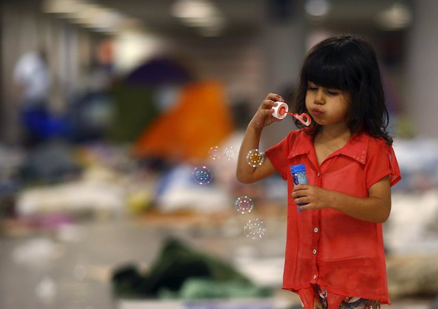 A migrant girl plays in the Keleti subway station after most migrants have left for buses bound for Austria and Germany, in Budapest, Hungary, September 5, 2015. (Photo by Leonhard Foeger/Reuters)