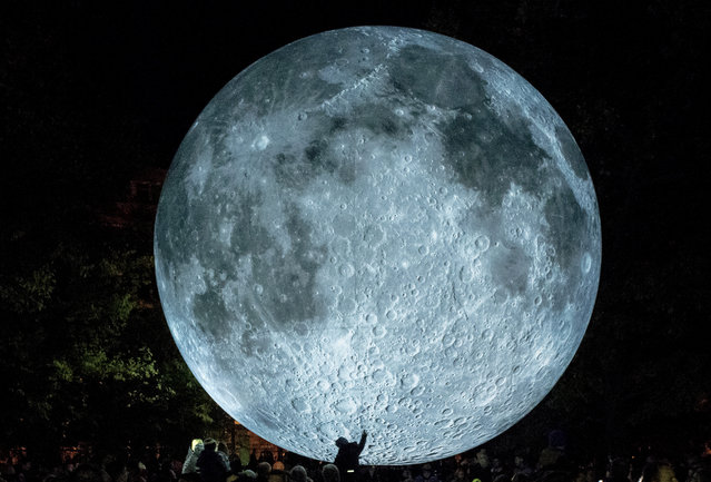 """A child is touching a light object called """"The Museum of the Moon"""" created by British artist Luke Jerram and displayed at the Medical Garden in Bratislava on October 7, 2017, during the White Night festival. (Photo by Joe Klamar/AFP Photo)"""