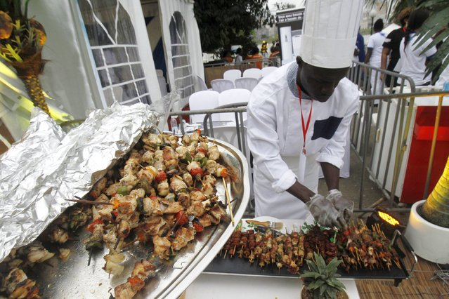 A cook prepares grilled meat during the Festival des Grillades, in the yard of the Culture Palace of Abidjan, September 5, 2015. (Photo by Luc Gnago/Reuters)