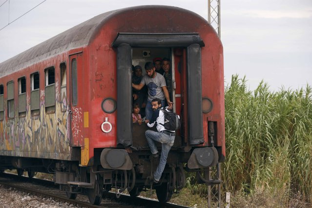 A migrant catches up with a train which has already left the station near Gevgelija, Macedonia, September 7, 2015. (Photo by Stoyan Nenov/Reuters)