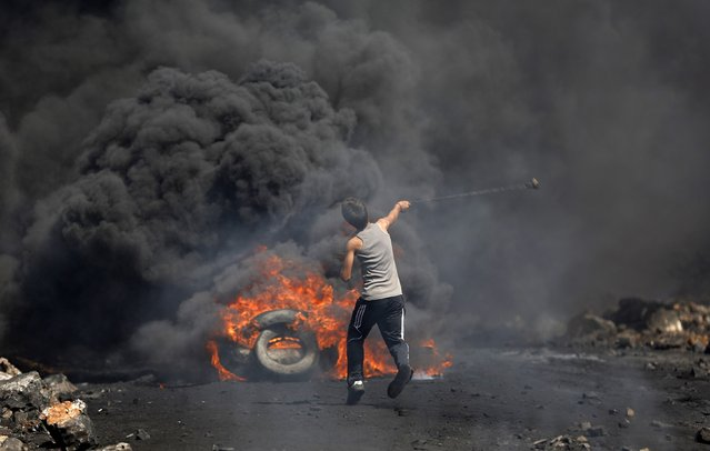 A Palestinian protester uses slings to hurl a stone toward Israeli soldiers as he stands next to burning tyres during clashes following a protest against the near-by Jewish settlement of Qadomem, in the West Bank village of Kofr Qadom near Nablus September 26, 2014. (Photo by Mohamad Torokman/Reuters)