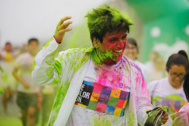 A participant is covered in colored powder as he compete in The Color Run in Lima, Peru, August 14, 2016. (Photo by Guadalupe Pardo/Reuters)