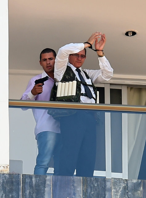 An unidentified man keeps a hotel employee with an explosive-laden vest at a balcony of the hotel in Brasilia on September 29, 2014. (Photo by Evaristo Sa/AFP Photo)
