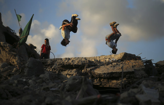Palestinian youths practice their Parkour skills over the ruins of houses, which witnesses said were destroyed during a seven-week Israeli offensive, in the Shejaia neighborhood east of Gaza City October 1, 2014. (Photo by Mohammed Salem/Reuters)
