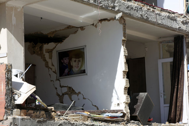A framed picture of a boy hung on a wall inside a partially collapsed building is seen in Sarpol-e Zahab town of Kermanshah, Iran on November 13, 2017 following a 7.3 magnitude earthquake that hit the Iraq and Iran. (Photo by Fatemeh Bahrami/Anadolu Agency/Getty Images)