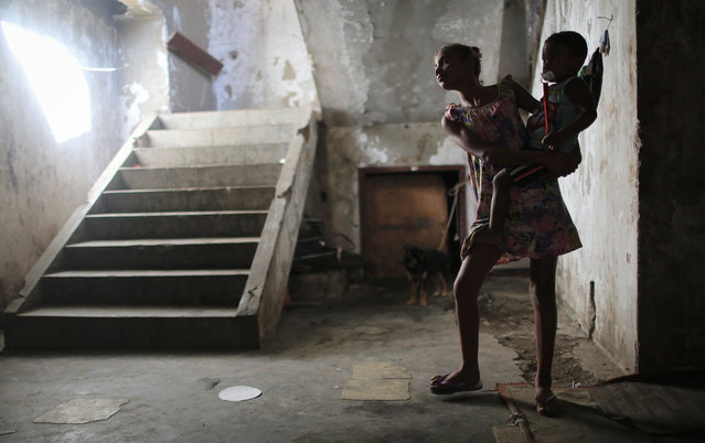 "Resident Taina holds her brother Ysaque in the hallway outside their apartment in an occupied building in the Mangueira ""favela"" community on August 13, 2016 in Rio de Janeiro, Brazil. (Photo by Mario Tama/Getty Images,)"