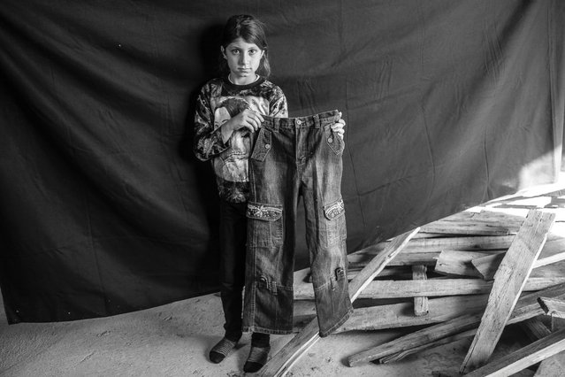 Leila (name changed for protection purposes), 9, poses for a portrait in the urban structure where she and her family are taking shelter in Erbil, in the Kurdistan Region of Iraq, on 17 November 2012. Together with her four sisters, mother, father and grandmother, Leila arrived in Erbil five days before this photograph was taken, after fleeing their home in Deir Alzur, Syria. Her family is one of four living in an uninsulated, partially-constructed home; there are about 30 people sharing the cold, draughty space.  (Photo by Brian Sokol/Panos Pictures)