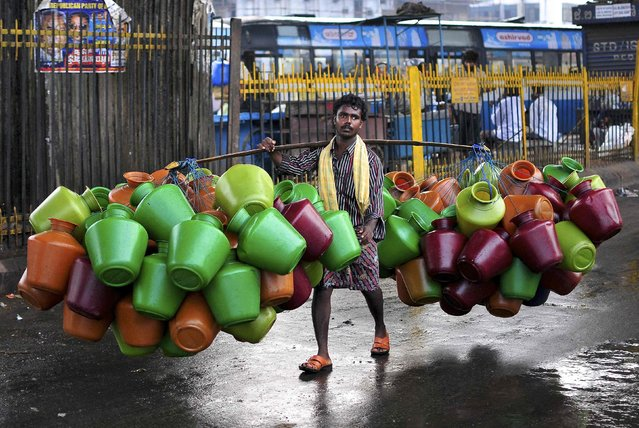 A man carries empty water pitchers for sale in a market in the southern Indian city of Bangalore October 9, 2014. (Photo by Abhishek N. Chinnappa/Reuters)