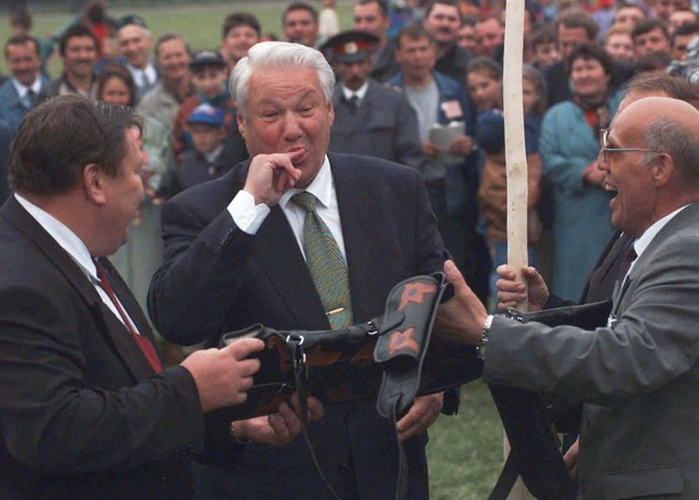 """Two local Tatar officials present Russian President Boris Yeltsin, center, with a covered rifle after Yeltsin played a traditional Tatar game of break the clay pot Sunday, June 9 1996 in the town of Arsk some 37 miles (60km) from the Tatar capital of Kazan. The game was part of the Tatar festival """"Sabantui"""" – the celebration of the plough. (Photo by Alexander Zemlianichenko/AP Photo)"""