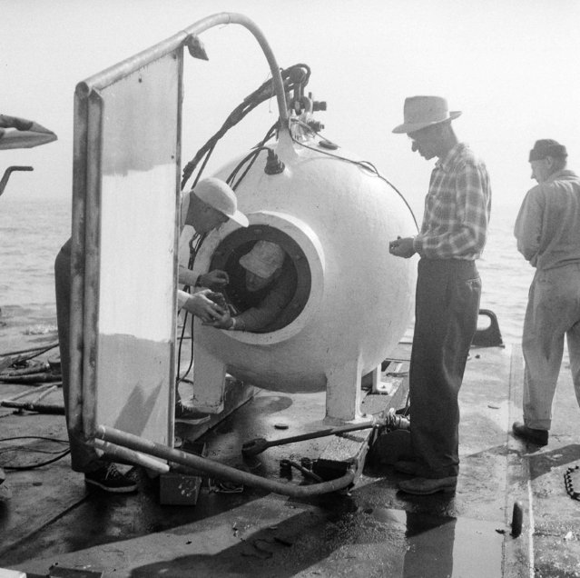 Diver Otis Barton, who hopes to break his own record for descents into the sea, leans from the steel diving bell as he prepared for a practice dive, September 24, 1952, on Catalina Island, Calif. Talking to Barton at left is Dr. Maurice Nelles, his technical advisory. At right is Perry Stille, electronic communications expert. The descents are made from a barge off the island. (Photo by AP Photo)