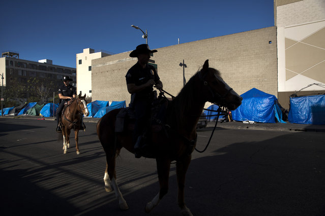 Tents belonging to homeless people are covered with tarps as Los Angeles police officers on horses patrol in the Skid Row area of downtown Los Angeles Friday, December 1, 2017. (Photo by Jae C. Hong/AP Photo)