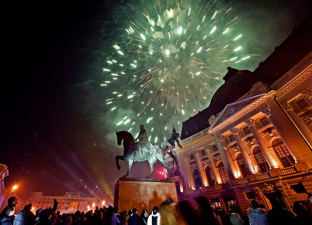 Fireworks explode above the statue of King Carol I in downtown Bucharest, Romania. (Photo by Vadim Ghirda/Associated Press)