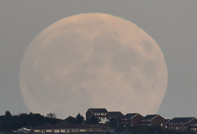 """A """"supermoon'' rises above Brighton in southern England September 27, 2015. Sky-watchers around the world are in for a treat Sunday night and Monday when the shadow of Earth casts a reddish glow on the moon, the result of rare combination of an eclipse with the closest full moon of the year. (Photo by Toby Melville/Reuters)"""